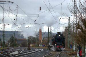 Dumpflokomotive neben Schiensträngen und Schornstein im Hintergrund