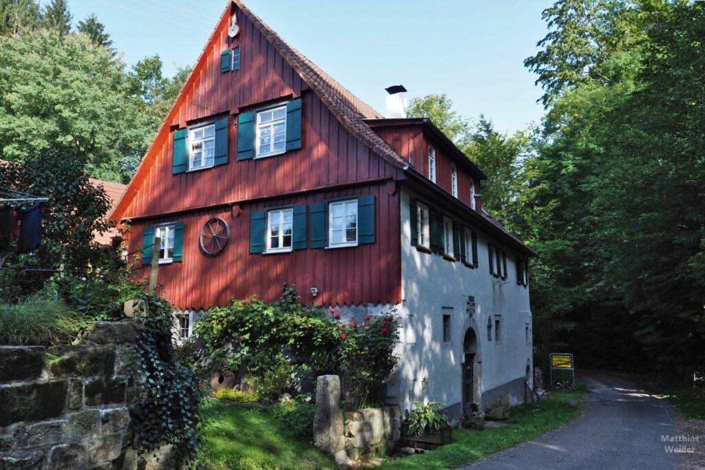 Mühlenhaus mit Holzfront neben Waldeinfahrt