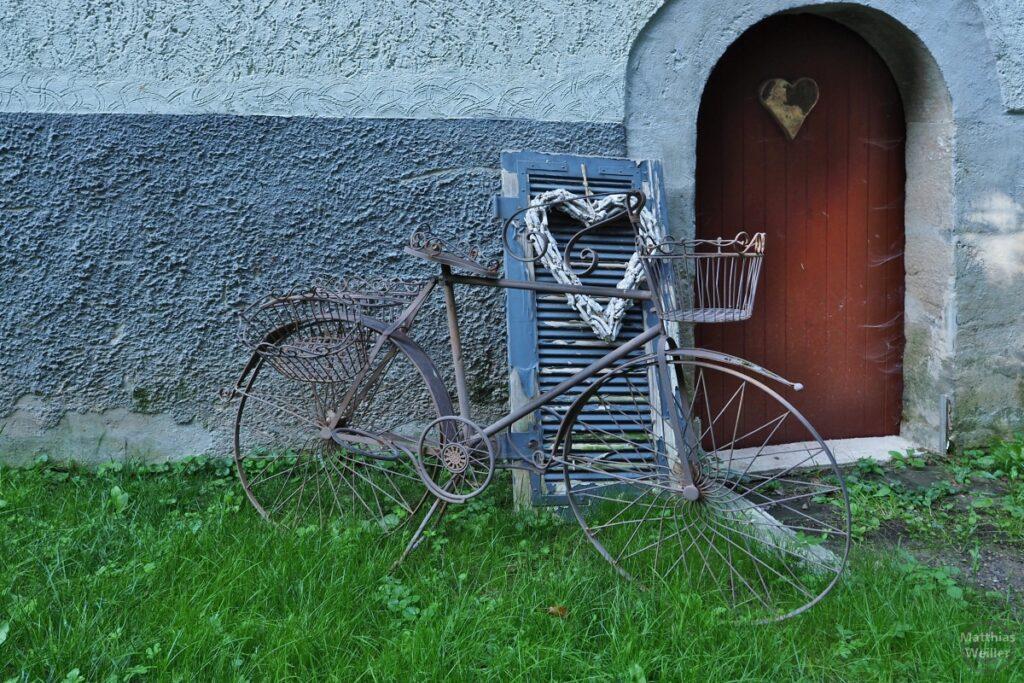 Schlichte Radskulptur aus Stahl mit Rundtür und Herz sowie angelegter Fensterlade mit Herz
