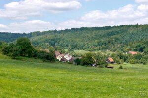 Typsiche Wald-Wiesenlandschaft der Limpurger Berge mit Dorf in der Talmulde