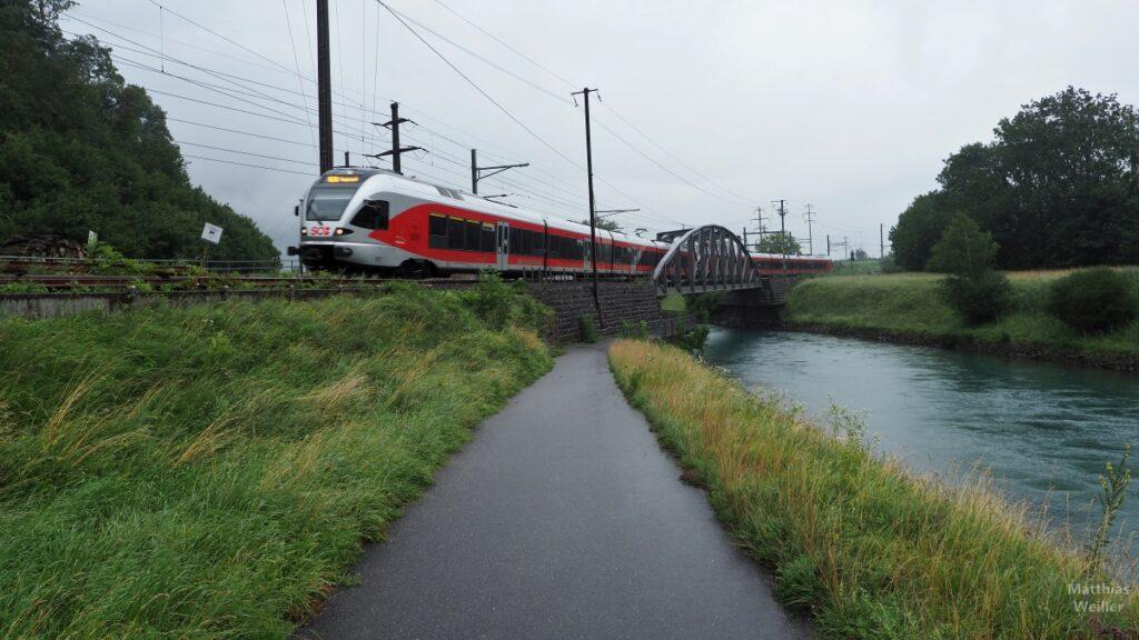 Triebwagenzug rot/grau über Brücke Linthkanal