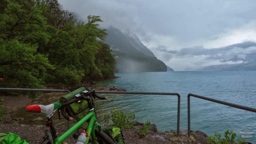 Blick über Geländer auf wolkenverhangenen Walensee, mit Reisevelo im Vordergrund