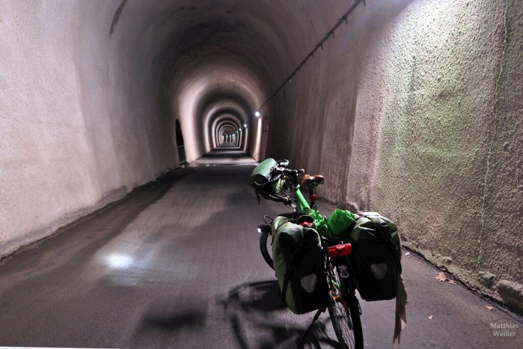 Radwegtunnel am Walensee mit grünem Reisevelo innen, mit Beleuchtung