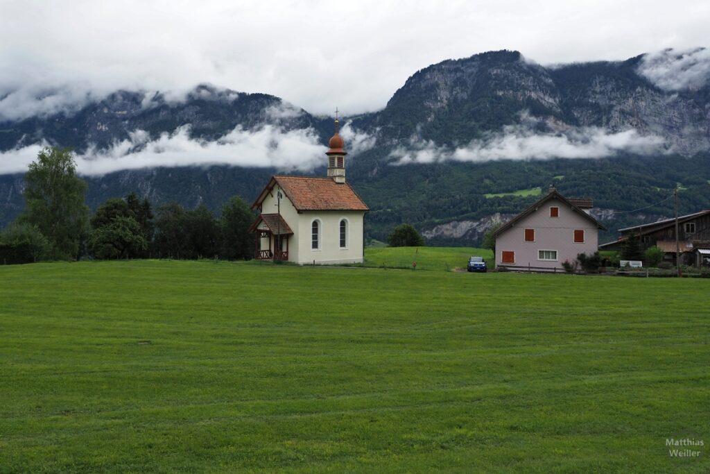 Kapelle mit Bergwiese davor, niedrige Wolke an Berghang dahinter