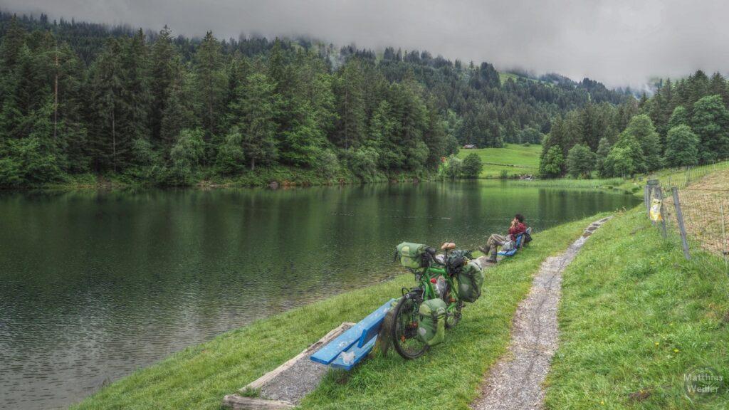 Chapfensee mit grünem Reisevelo an blauer Bank, Mann auf zweiter Bank dahinter