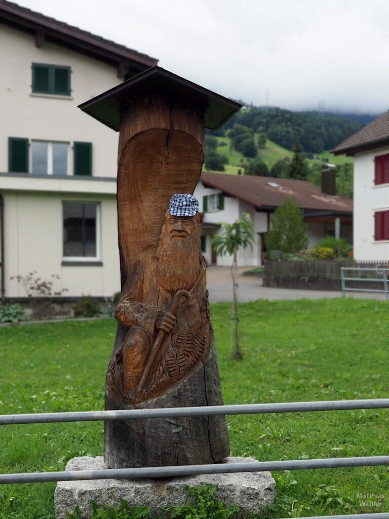 Holzshcintzsäule mit bärtiger Figur, Gehstock und karierter Mütze