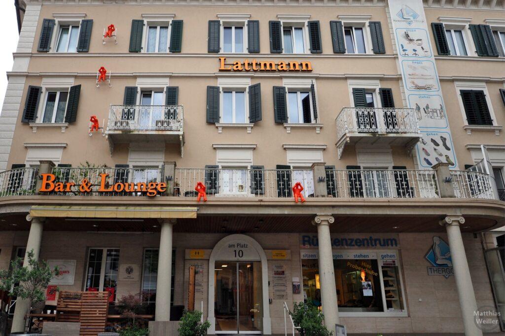 Orangene Späherskulpturen auf Hausfront verteilt