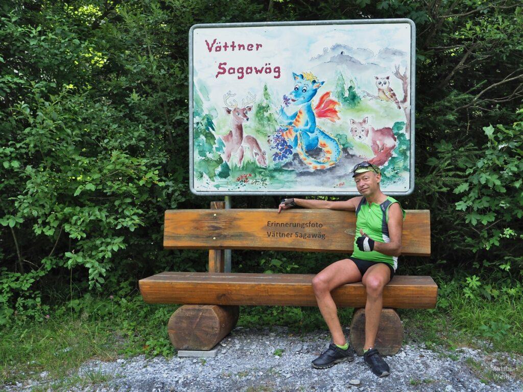 """Selber auf Bank """"Erinnerungsfoto Vättner Sagawäg"""" sitzend, Deumen nach oben, bunte Tafel zum """"Vättner Sagawäg"""""""