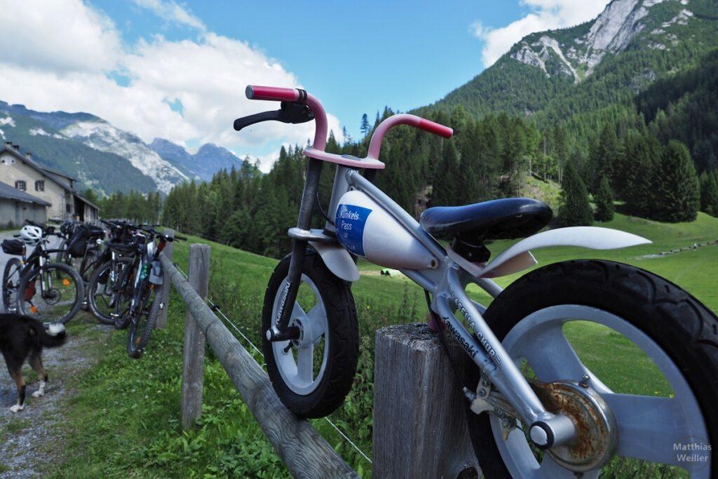 Kunkelspassschild auf Spielzeugmotorrad auf Holzzaun, Velos