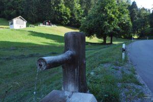 Nahaufnahme Holzbrunnen vor Bergwiese mit Hütten nebst Straße