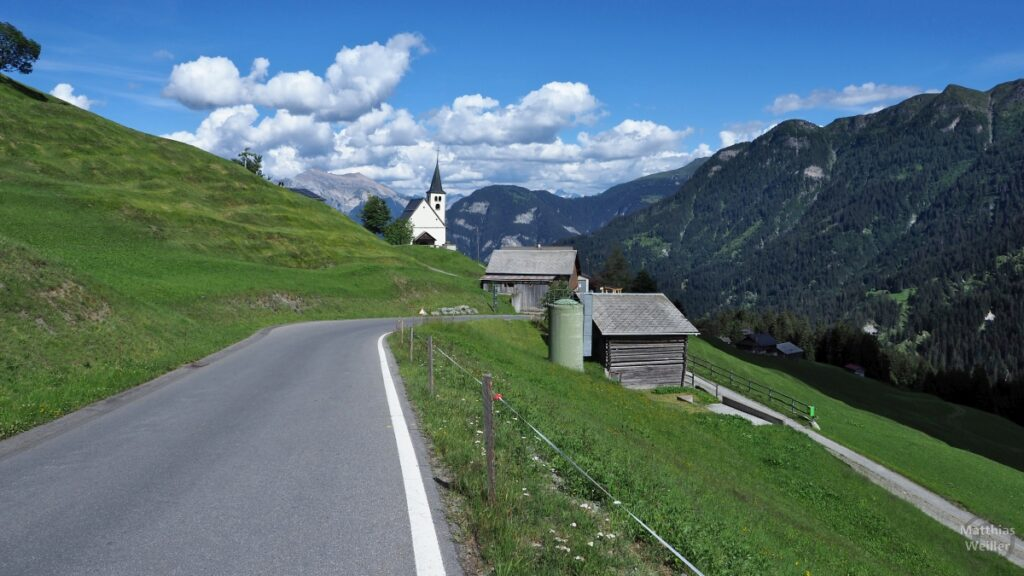 Kirche Tschappina mit grünen Bergwiesen und Berghorizont