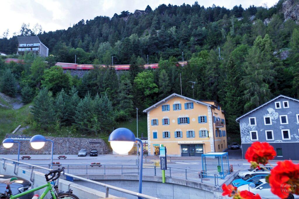 Blick von Terrasse auf überhöhte Bahntrasse, Häuser, Straßenlampen