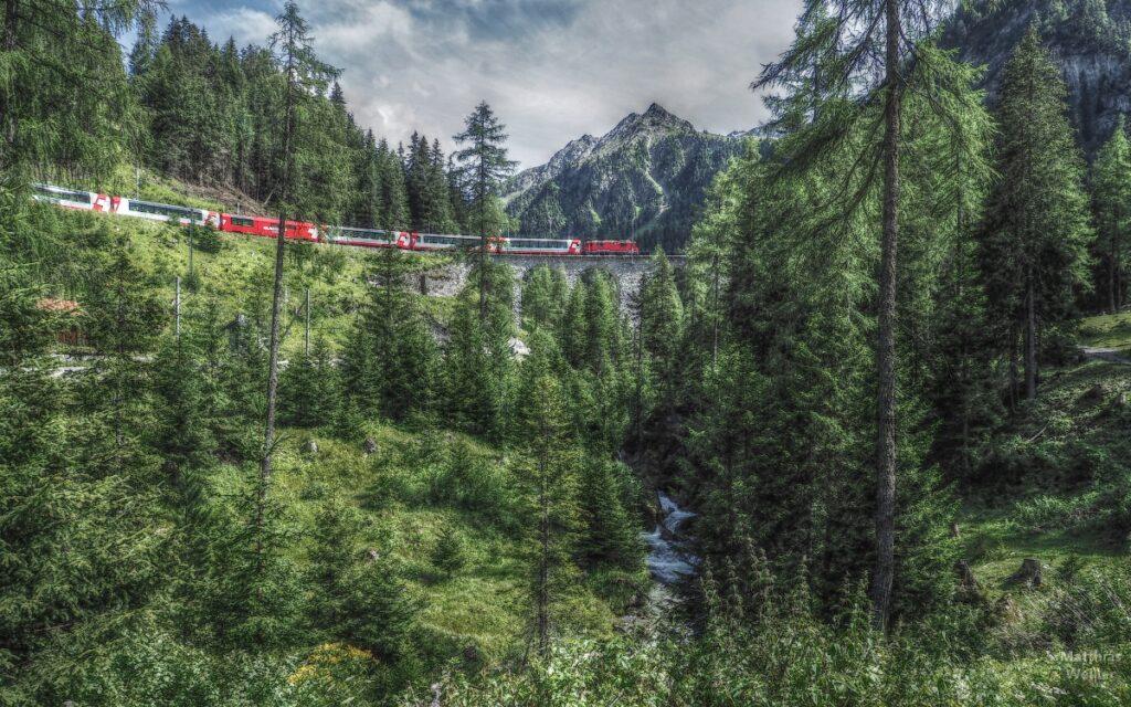 Bahnviadukt mit Bahn rot/weiß, mit Lärchenwald und Berggipfel