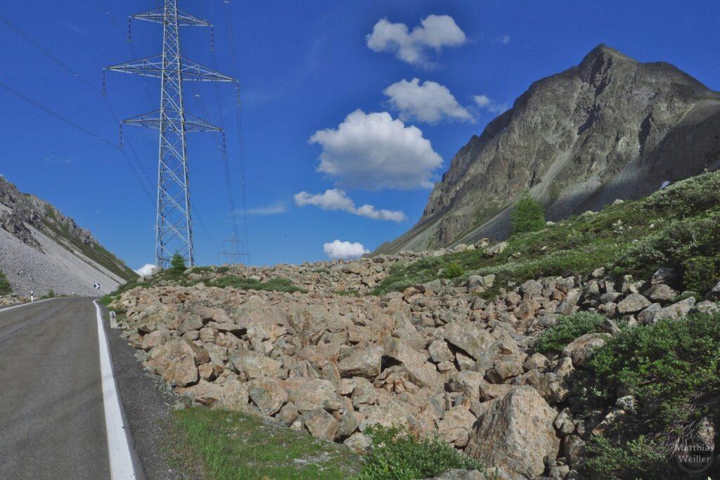 Geröll mit Berg, Strommast und Straße