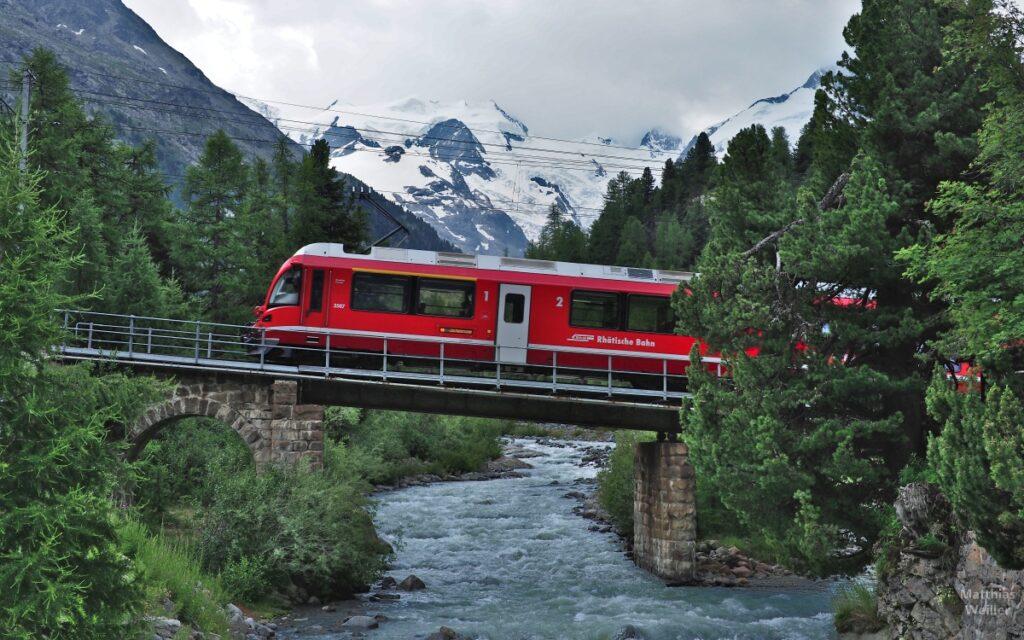 Roter Bahntriebwagen mit Velosymbol über Bergbach mit Gletscherkulissse