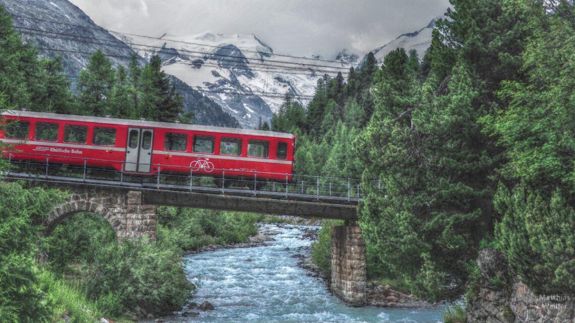 Roter Bahnwagen mit Velosymbol über Bergbach mit Gletscherkulissse