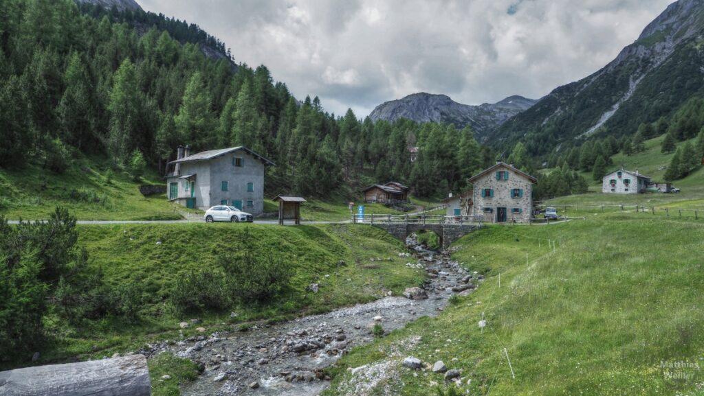 Häuser mit Bergbach am Fuße Val Trela