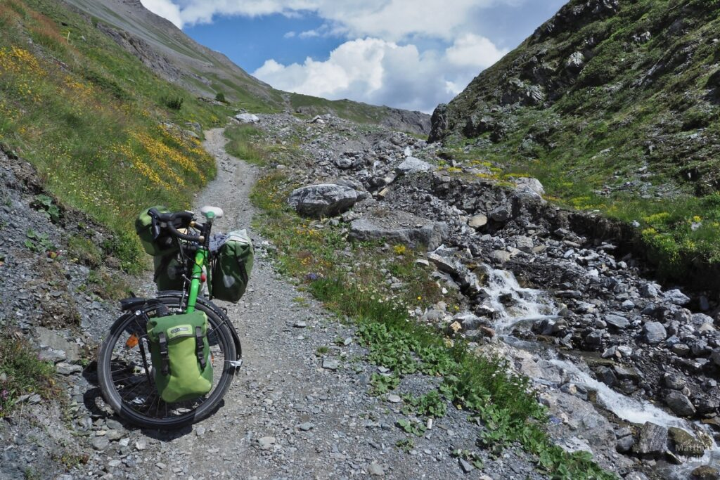 Trail mit grünem Reisevelo neben Bergbach