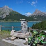 Grünes Resievelo mit BRunnen vor See San Giacomo und Kegelbergen