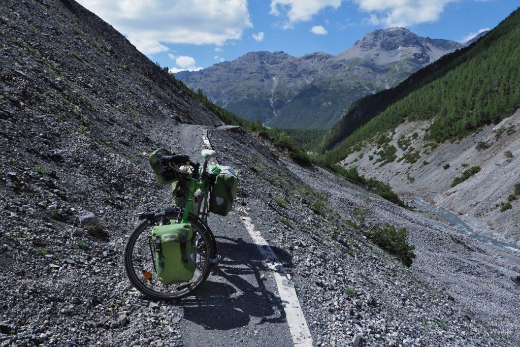 Gruüens Resievelo auf Gerölltrail mit Bergkulisse im Val Mora