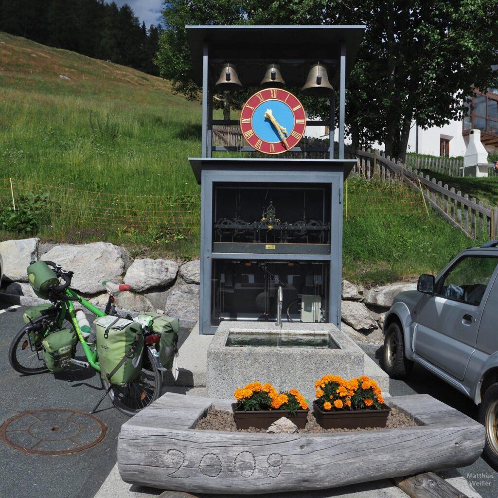 Tranparente Zuguhr mit drei Glocken vor Brunne in Lüsai, mit grünem Reisevelo