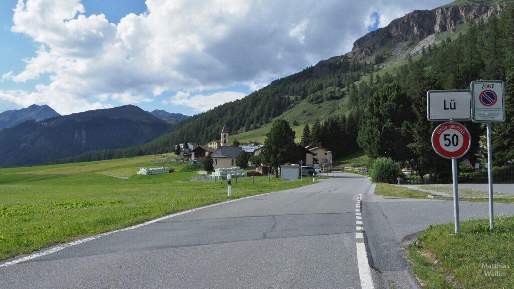 Ortschild Lü mit Dorf im Hintergrund