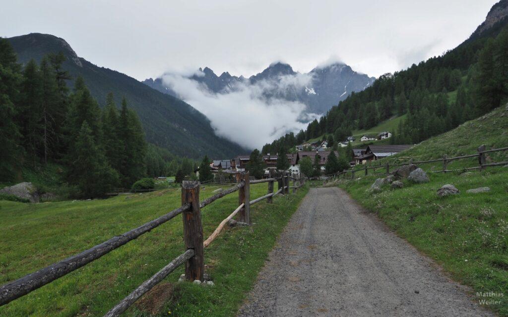 Anfahrt auf S-charl mit Bergen bei tiefhängenden Wolken