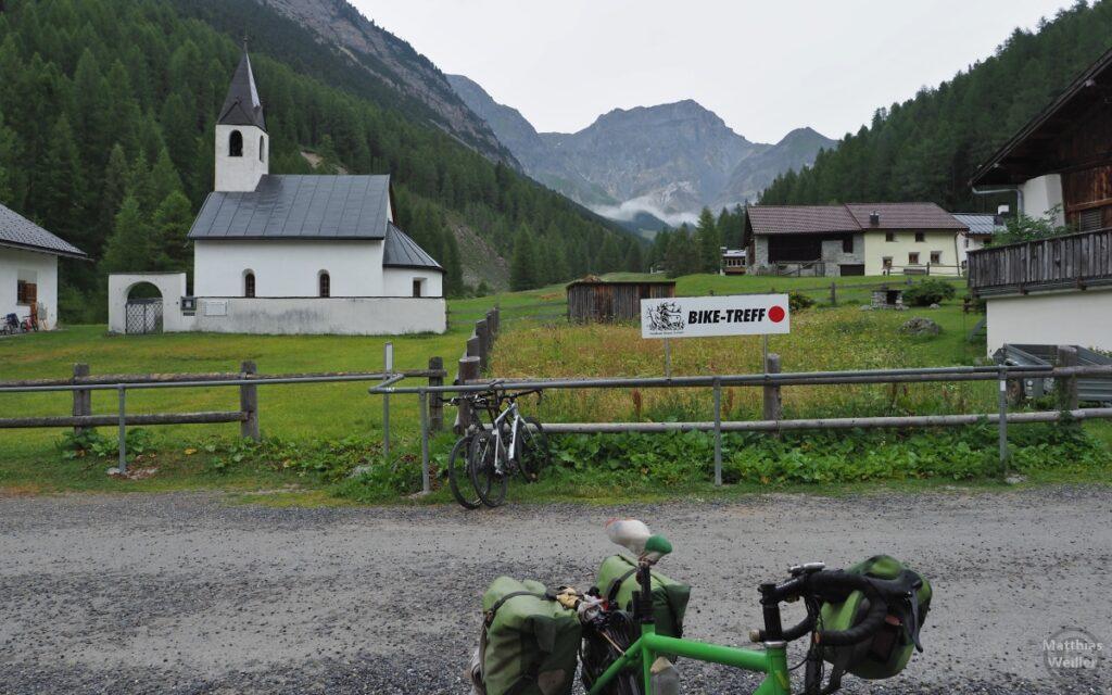 """Kleine Kirche vor Bergkulisse, """"Bike-Treff"""" mit Velos im Vordergrund"""