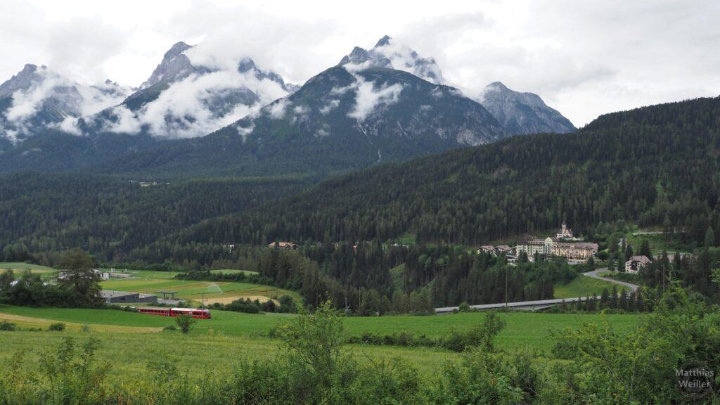 Blick ins Inntal mit woklenverhangenen Bergen und Bahn