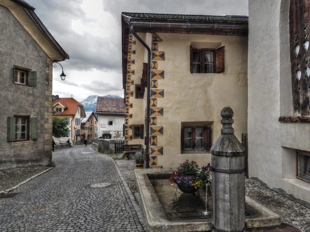 Dorfszenerie Guarda mit Holzbrunnen