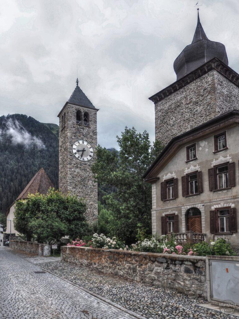Steinmauerkirchtum nebst Zwiebelturm und Engadinerhaus