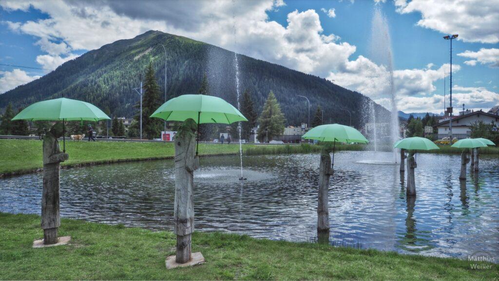 Holzskulpturen mit grünen Schirmen und Wasserfontänen, Kurteich Davos