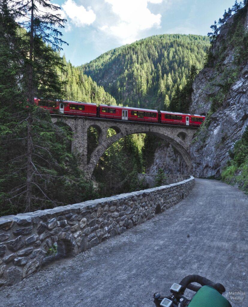 Rote Bahn auf Viadukt in Zügenschlucht, aus Tunnel kommend