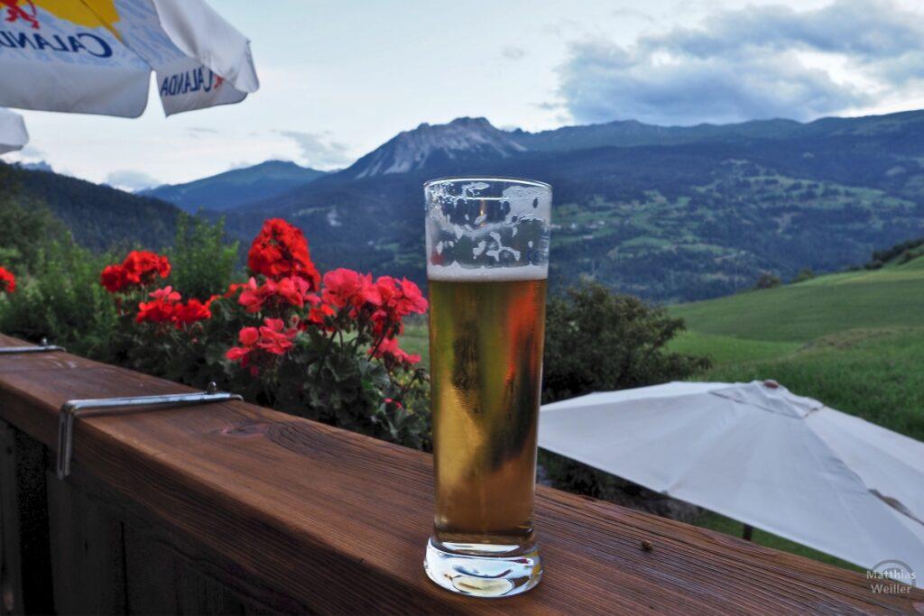 Bier auf Holzbalken, mit Geranie, Albulatal im Hintergrund