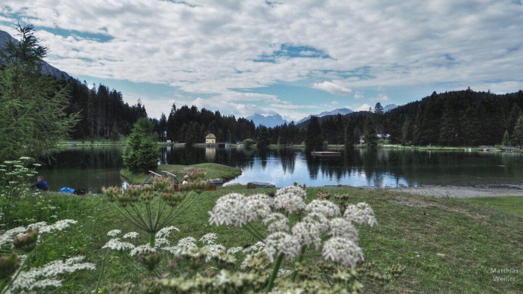 Blick auf Heidsee über Dolde mit Kapelle und Bergen im Hintergrund