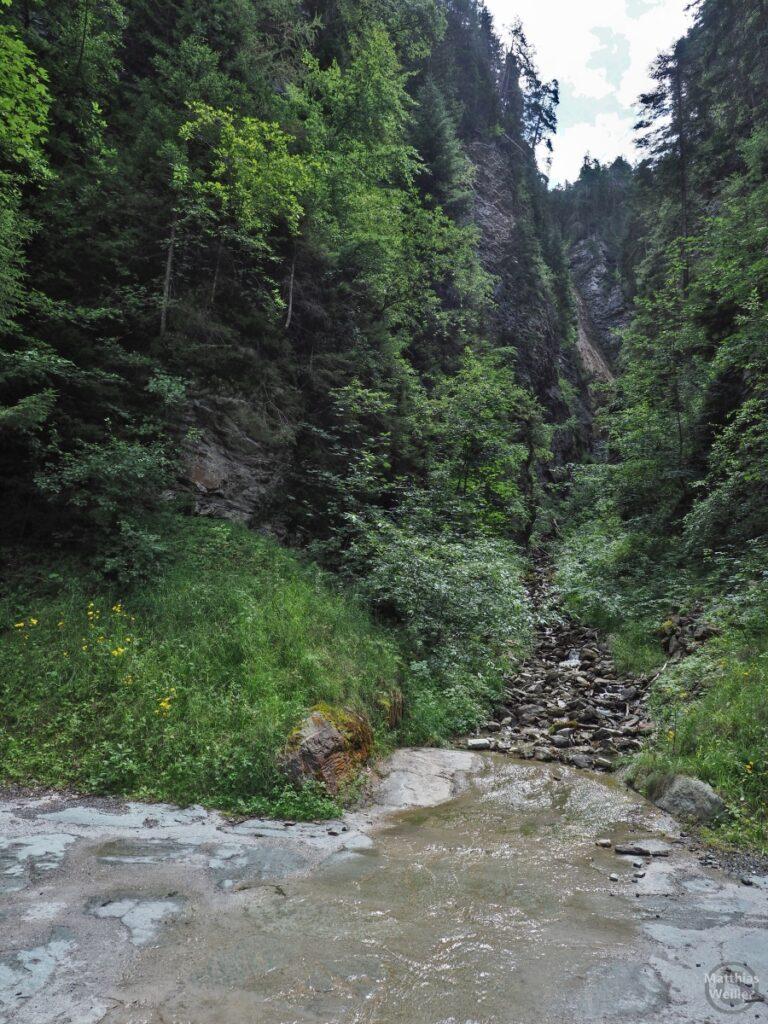 Geröllabgang an Straße mit Bergbachüberlauf