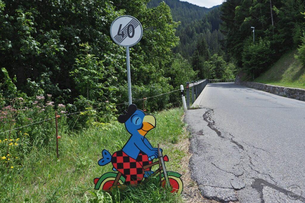 Comicfigur mit Velo, bunt, an Straße mit Schild für Geschwindigkeitsbeschränkungsaufhebung