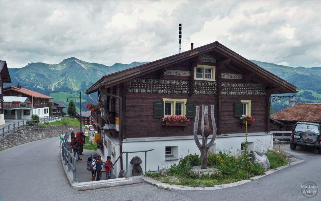 Berghaus Tschiertschen mit Plessurtal im Hintergrund und Feriengästen mit Rucksäcken