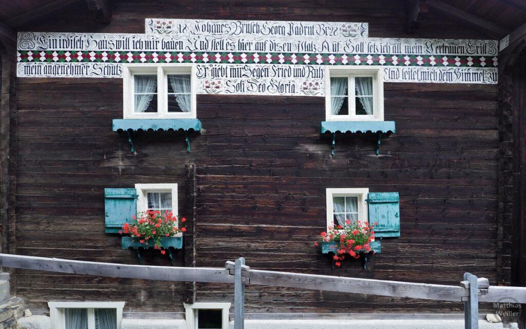 Holzfassade mit blauen Fesnter, roten Geranien und Spruchband auf weißem Grund über den Fenstern