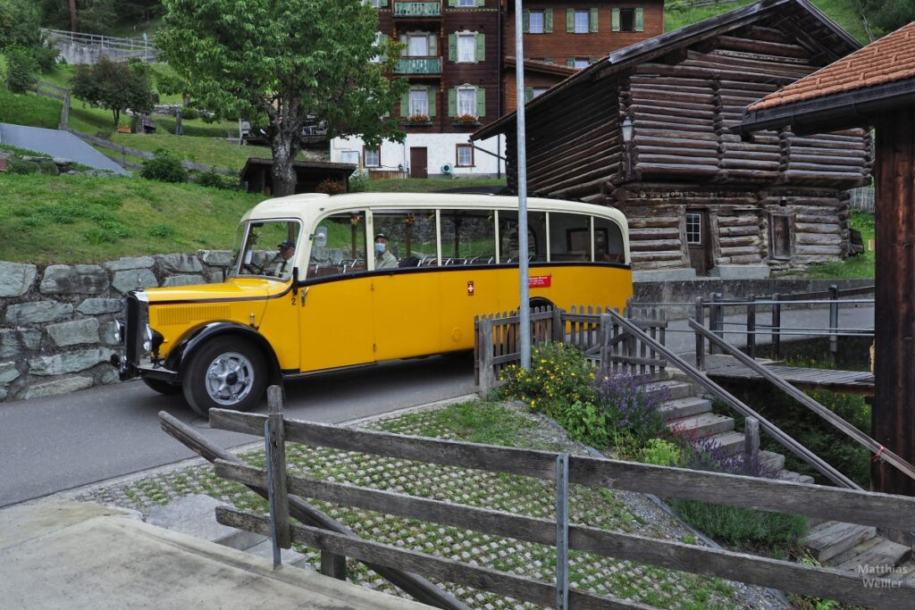 Nostlagischer Schweizer Postbus vor Dorfhäusern mit Gärten