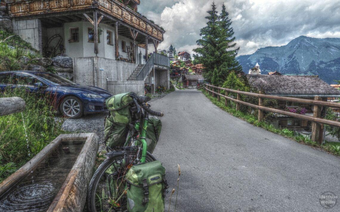 Stilisertes Bild mit Brunnen, grünem Reisevelo Haus, blaues Auto und Dorf Tschiertschen