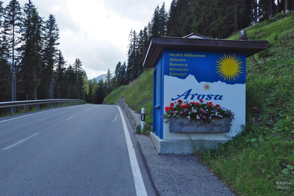 Willkommens-Pavillon Arosa mit großer Sonne auf blauem Grund, an Straße