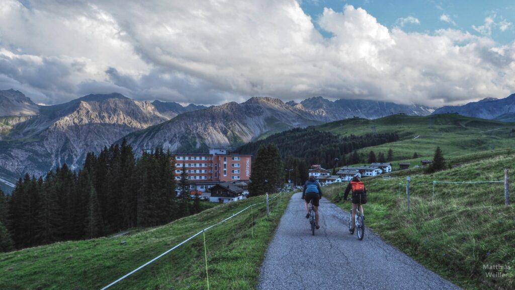 Blick von Fahweg über 2 Radler und Plätschli-Hotel mit Bergkulisse