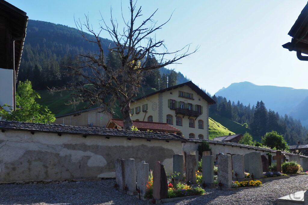 Blick über Friedhof auf Berghaus und Berge in Langwies
