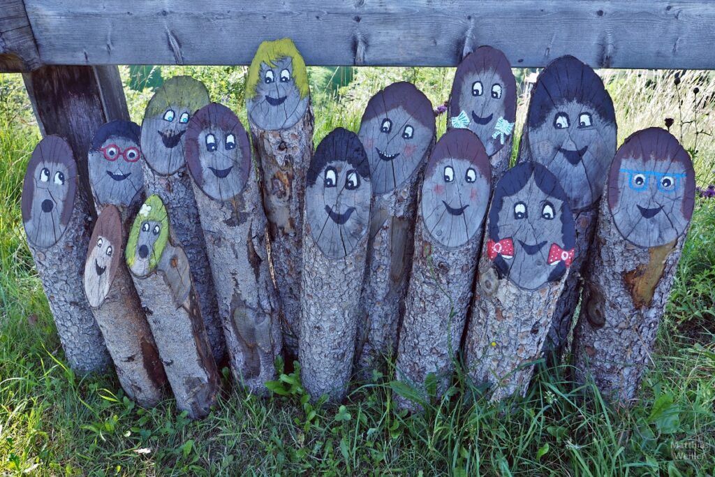 Dünne Holzstämme als Personengruppe mit lustigen Gesichtern