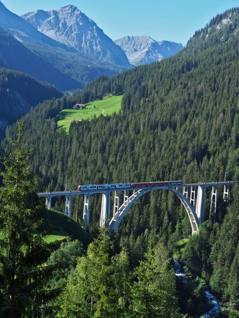 Langwieser Viadukt mit Zug rot/weiß vor Bergkulisse