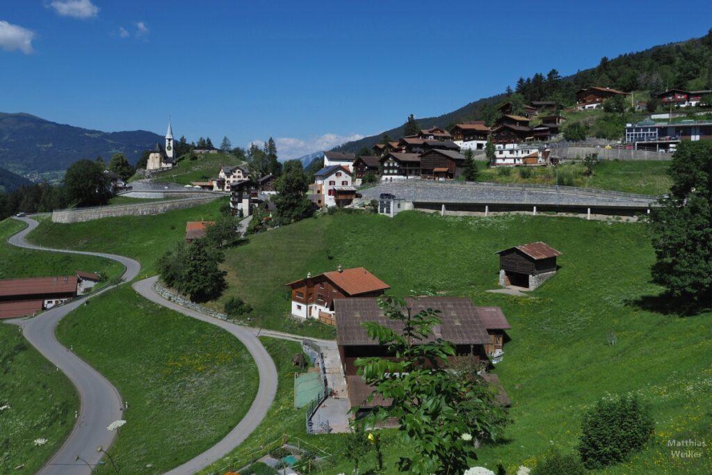 Bergdorf an Hang mit Kirche und Kurven