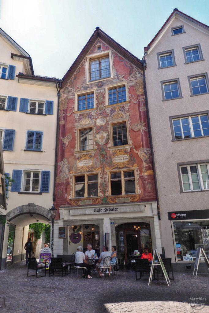 Bunt bemalter Giebelhaus, Rot- und Goldtöne mit Cafetischen/-gästen