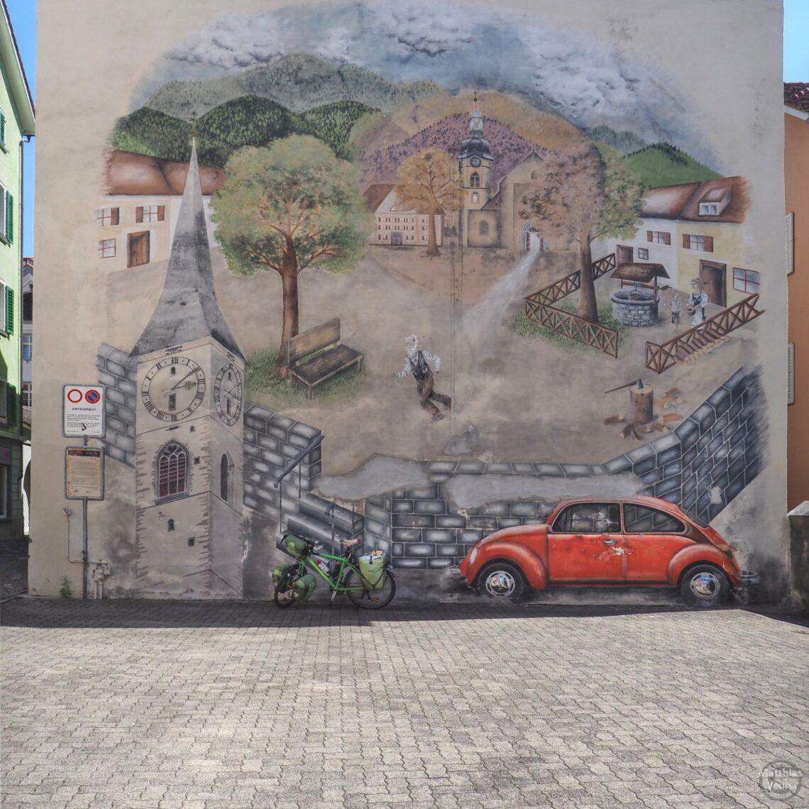 Fassadenbild mit Geschichtshintergrund der Stadt Chur, gemalter VW-Käder rot, grünes Reisevelo real