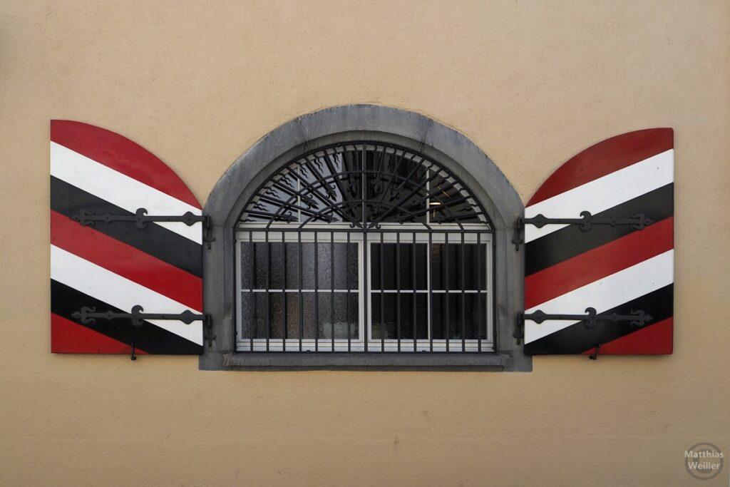 gebogesn Gitterfenster mit Läden in rot/weiß/schwarz